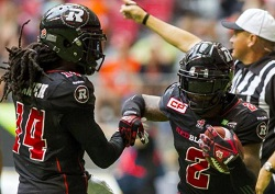 Ottawa Redblacks' Jovon Johnson celebrates an interception against the B.C Lions with teammate Abdul Kanneh during the second half of their CFL football game in Vancouver
